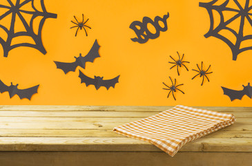 Empty wooden table with tablecloth over Halloween holiday decorations background