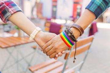 Happy lesbian couple wearing rainbow bracelet