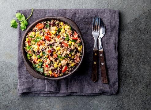 Mexican black bean corn quinoa salad in clay bowl top view, copy space