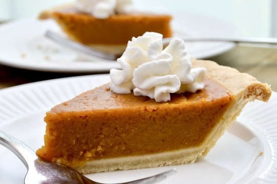 Slice of pumpkin pie with whipped cream on a white plate with fork