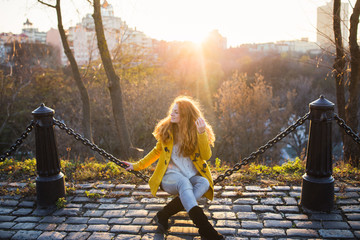 Red hair beautiful woman wearing yellow coat walking outdoors. Autumn time, city on background