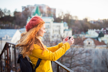 Red hair beautiful woman wearing yellow coat and orange beret with backpack walking outdoors. Autumn time, city on background