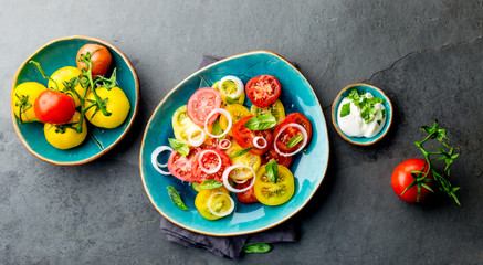 Red and yellow fresh tomato salad with onion, basil and white sauce on blue plate. Gray slate background, top view