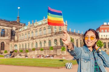 girl traveler having fun in Dresden with rainbow flag symbol. Free love relationship concept