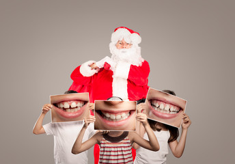 Santa Claus with a group of happy children holding a picture of a mouth smiling