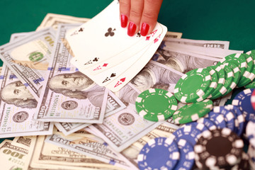 Woman playing poker with cards, chips and cash on the green casino table