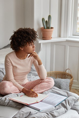 Comfort, rest, inspiration concept. Thoughtful black woman with pen, book and notebook, writes somethning in bed, prepares for exam, learns new information, creats up to date article, poses at home