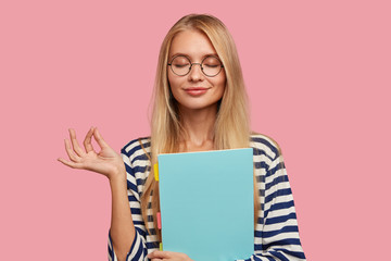 Photo of pleasant looking pleased blonde woman makes okay gesture, believes in something good, keeps eyes closed, dressed in casual clothes, isolated over pink background, reads informative book