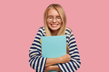 Happy overjoyed smiling teenager with blonde hair, keeps textbook closely, laughs at something funny, has break between classes, poses against pink background, dressed in striped sailor sweater