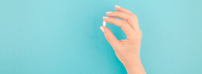 Female hand holding a white pill