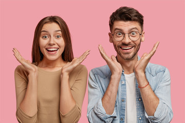 Studio shot of cheerful young people, clasp hands near face, rejoice positive moments in life, look joyfully at camera, dressed in casual clothes, isolated over pink background. Emotions concept