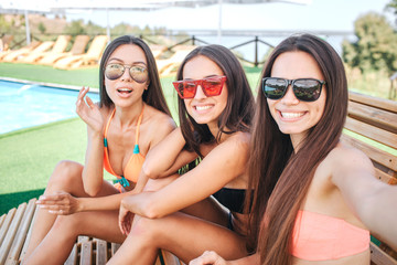 Picture of three models sits on sunbeds and smile. Woman on the right holds camera. Other two are just pose. Woman on the left looks amazed. All of them wear sunglasses.