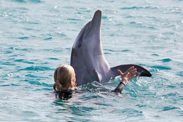 Delfin mit Frau im Meer