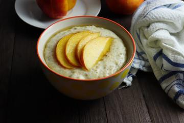 Oat porridge with sliced of nectarine and honey