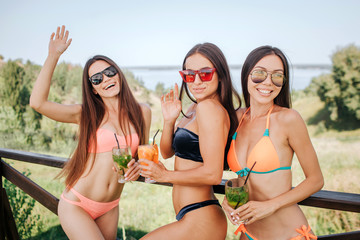 Well-built and gorgeous girls stand and pose on camera. They holds glasses with cocktails. Young women show different emotions, from seriousness to happiness.
