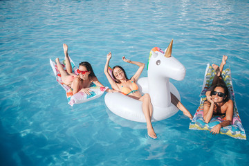 Picture of model are sitting and lying on floats in pool. They having rest. Two women lying on stomach and show their beautiful bodies. Model in middle stretching hands up and smiling