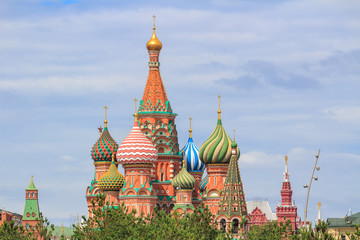 St. Basil's Cathedral on Red square in Moscow against green trees and sky with clouds on a summer day