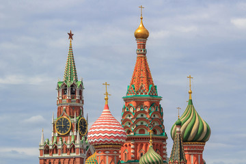 Onion domes of St. Basil's Cathedral on Red square against Spasskaya tower of Moscow Kremlin on a background of dramatic cloudy sky