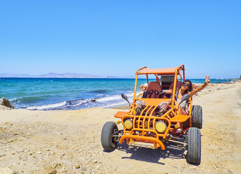 A happy girl driving a Buggy on a dune of beach with the Aegean sea in background. Greek island of Kos. South Aegean region, Greece.