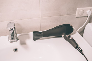 Picture of hair dryer on sink. It is connected to socket. Device is lying in bathroom.