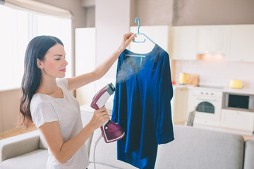 Woman is steaming blue shirt in room. She holds small stream iron in hand. Brunette is concentrated on work.