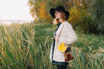 Hippie girl with a yellow maple leaf in a knitted sweater and hat walks autumn park.