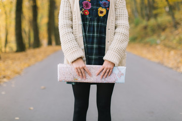 Hippie girl with a map, old camera in a knitted sweater and hat walks autumn park.