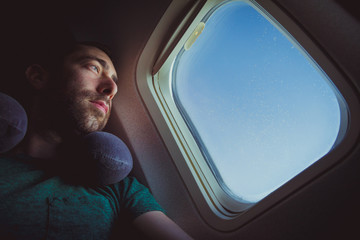 Pensive man with neck pillow looking outside through the window of an airplane