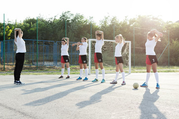 Young female handball players stretching