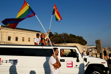 Participants wave rainbow flags from a Hummer Limousine during the Malta Pride Parade in Valletta