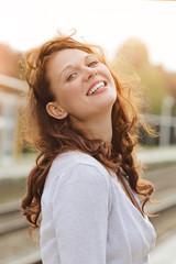 jolie jeune femme rousse souriante au soleil d'automneg