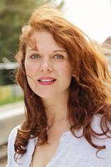 jolie jeune femme rousse souriante au soleil d'automne