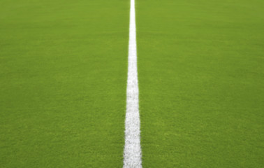 Defocused football / soccer field with White central line, Blur background ready for your design