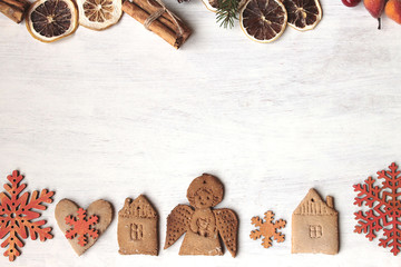 Christmas background with fir branches, decorations/figures  of angel, houses,heart, snowflakes/a gift boxes, cinnamon sticks,dry lemon,pine cones,artificial berries/ Space for text