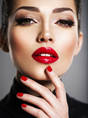Beautiful woman with bright make-up and red nails.