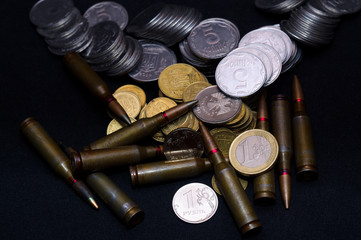 One euro, Russian ruble and small Ukrainian coins with rifle military ammo on black background. Symbolizes war for money- biggest problem in world.