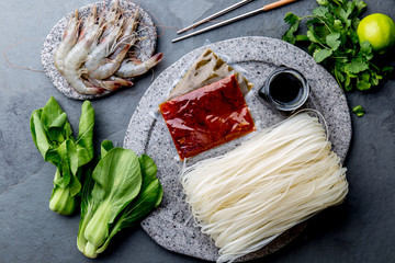 Asian cooking ingredients: rice noodles, pok choy, sauces, raw shrimps. Asian food concept Chinese or Thai cuisine.