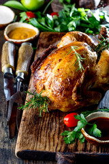 Baked whole chicken on wooden board. Close up