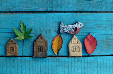 autumn background /  the figures of houses and birds made of dough with autumn leaves on blue wooden background