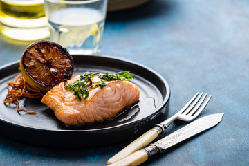 Salmon Sole Meuniere with lemon. Fillet of red fish. Steak trout fried with butter, lemon and parsley sauce