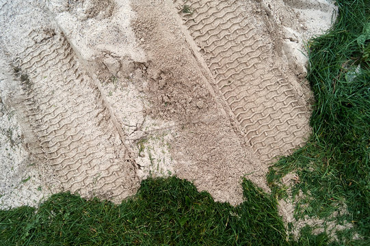 Tire tracks in the sand that was placed over the green grass during construction