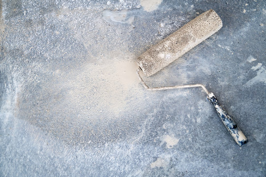 Dirty paint roller on the dirty concrete floor