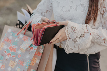 Woman with shopping bags holding a leather wallet. Concept of epmty purse after black friday sale