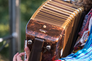 Close up of accordion player playing at Klezmer Jewish music concert in Regent's Park in London UK