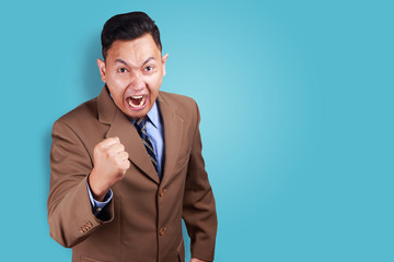 Angry Asian businessman showing his fist, ready to fight while screaming