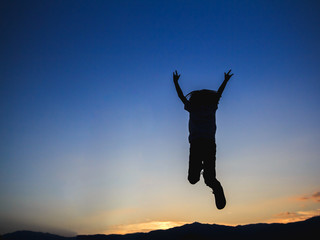 Silhouette of happy little girl jumping playing on mountain at sunset time