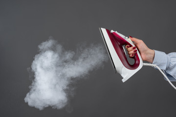 Woman holds an iron with steam on gray background