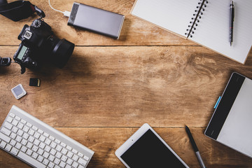 Top view vintage style of photographer consisting on a cameras, a keyboard, a smart phone, notebook on a wooden desk background