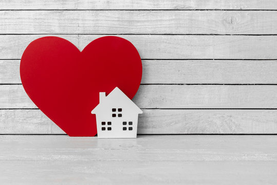 Home Shaped with Red Heart Shaped on white wood over white wood background