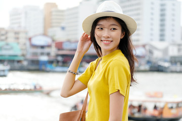 Young asian woman portrait smiling with happiness at city outdoors background, casual lifesyle, travel blogger